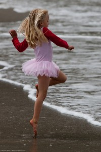 Cute Little Girl in Pink Dances on the Beach during the Kite Fes